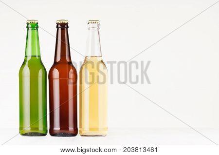 Brown green transparent longneck beer bottles 500ml mock up. Template for advertising design branding identity on white wood table.