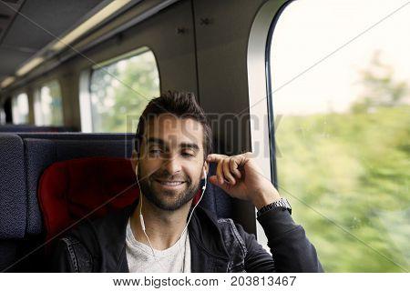 Dude listening to music through earphones on train