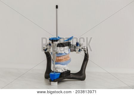 Articulator In A Dental Lab With Mold Or Artificial Denture In Dental Lab On White Background Close-