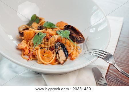 Seafood Pasta With Mussels And Basil In White Plate On Wooden Table.