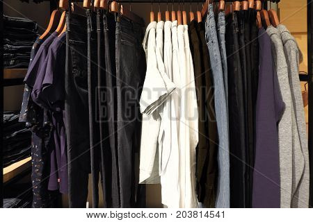 Clothes hanging on rack in shop. Clothes shop.