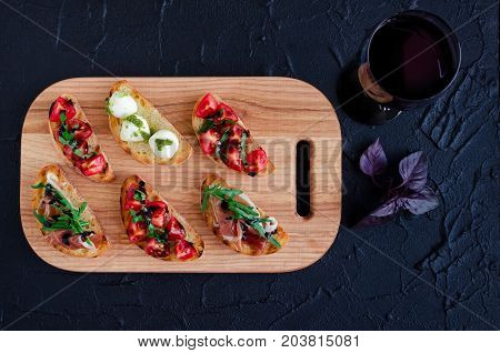 Brushetta set for wine. Variety of small sandwiches served with glass of red wine. Delicious snack appetizer antipasti on party or picnic time. Italian cuisine concept. Slow living. Top view.