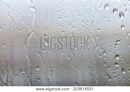 Rain drops on the glass. Drops of water on the glass. Rain falling on glass during rain storm close up.