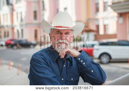 A mature cowboy in a hat jeans and a denim shirt looks at the camera. On open air