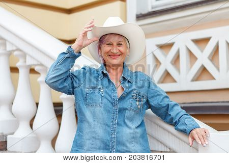 Elderly woman in cowboy hat looking at camera and smiling. On open air