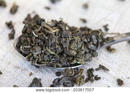 Spoon of dried green tea leaves on wooden background