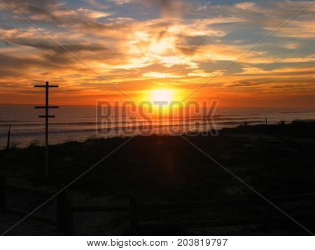 A SILHOUETTE IN THE FORE GROUND, WITH THE GOLDEN RED RAYS OF THE SUN, SETTING IN THE BACK GROUND 01