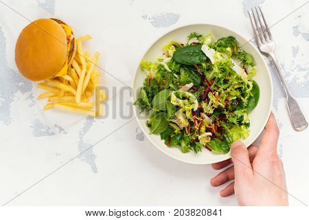 Young man making choice between healthy salad and fast food. Diet or healthy lifestyle concept