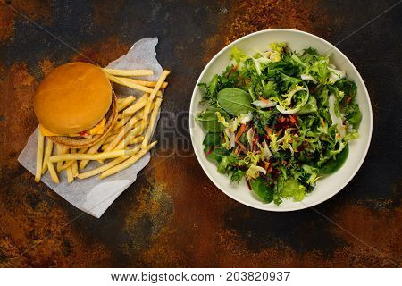 Making choice between healthy salad and fast food. Diet or healthy lifestyle concept