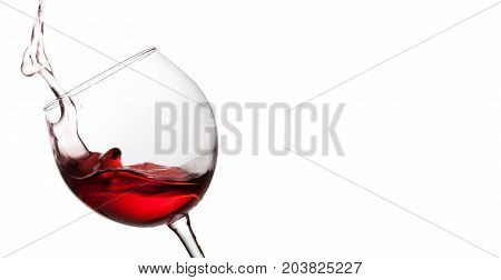 Splashing red wine in crystal wineglass. white background. copy space.