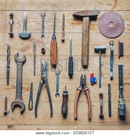 Collection of old dirty vintage repair tools well organized on wooden background, top view deliberate high contrast picture