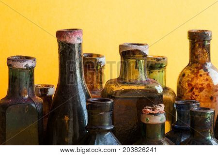 Vintage bottles close-up. Colorful dirty glass flacon set. Soft yellow orange background, shallow depth of field