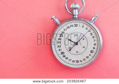 Retro style stopwatch chronometer on pink paper textured background. Sport competition time management concept. Macro view, soft focus photo