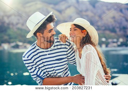 Happy young couple walking by the harbor of a touristic sea resort