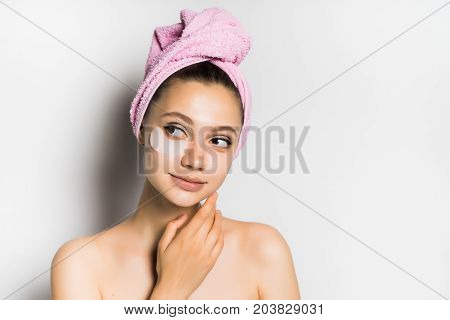 Young beautiful woman after bathing with a towel on her head, looking after the skin, looking with interest to the left