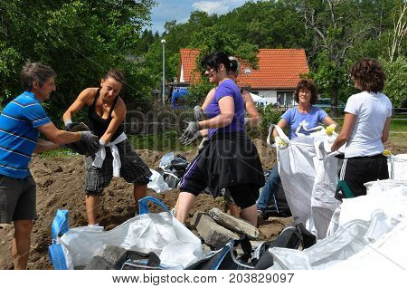 JERICHOW, GERMANY - JUNO 16, 2013: Women and men fill special bags with stones. They are later throw from a helicopter to close the hole in a broken dike. (Flood 2013, Saxony-Anhalt