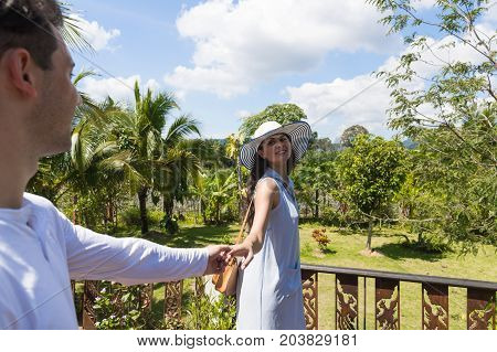 Young Couple On Summer Terrace Or Balcony Cheerful Woman Leading Man To Enjoy Beautiful View Of Tropical Forest