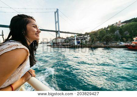 Happy young traveler girl smiling in full view, sunset on the Bosphorus. Modern bridge