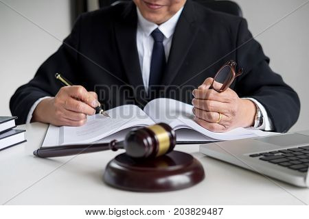 lawyer hand writes the document in court (justice law) with sounding block.