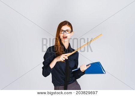 Young woman teacher pointing a ruler to somewhere holding a blue folder with documents, smiling, looking at the camera