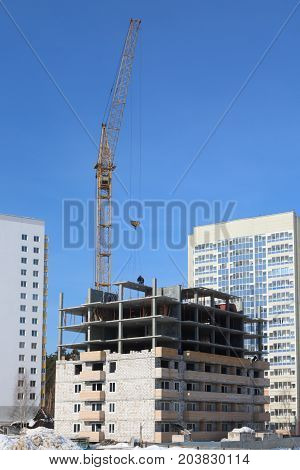 Unfinished high-rise building and working crane at sunny winter day