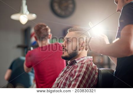 Low angle portrait of a handsome young man talking to his barber while getting a new haircut.
