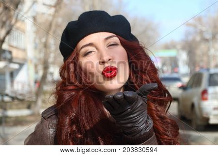 Young woman in leather gloves and beret sends air kiss on street at sunny spring day