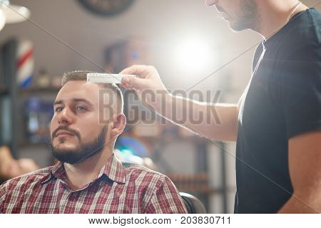 Professional barber using a comb while styling hair of his male client.