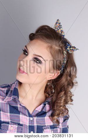 Pinup beautiful young woman in checkered shirt and with curly hair in studio