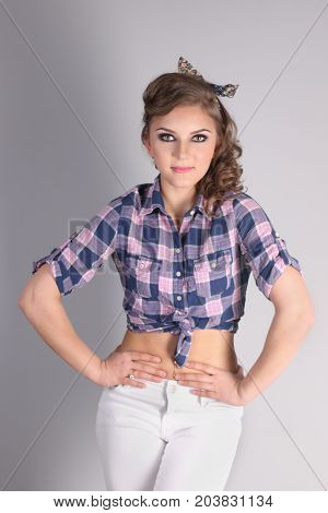 Pinup beautiful young woman in checkered shirt and with curly hair poses in studio