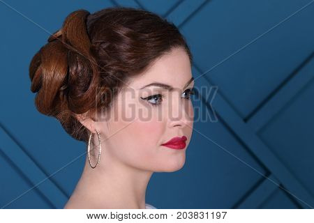 Beautiful woman with hairdo looks away in blue studio close up portrait