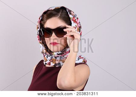 Beautiful woman in sunglasses and shawl poses in grey studio
