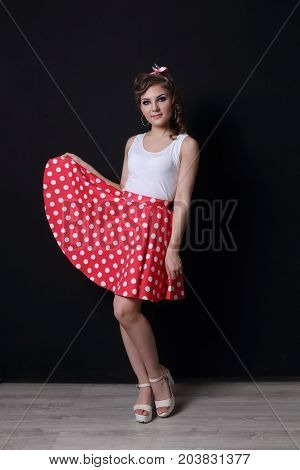 Pinup beautiful woman in red skirt and with curly hair poses in black studio