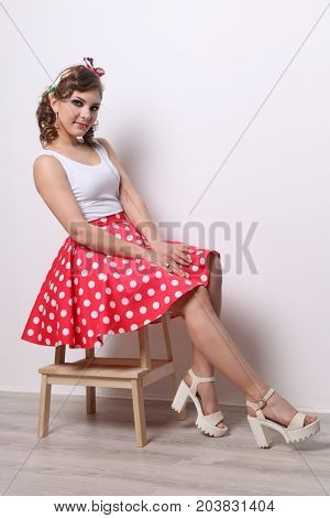 Pinup pretty girl in red skirt poses on wooden stool in studio