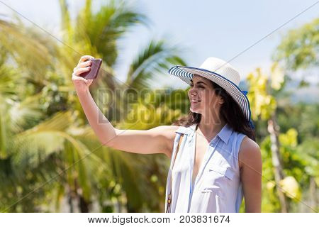 Beautiful Woman In Hat Making Selfie Photo Portrait Over Tropical Forest Landscape Happy Smiling Cute Girl Making Self Picture Over Palm Trees