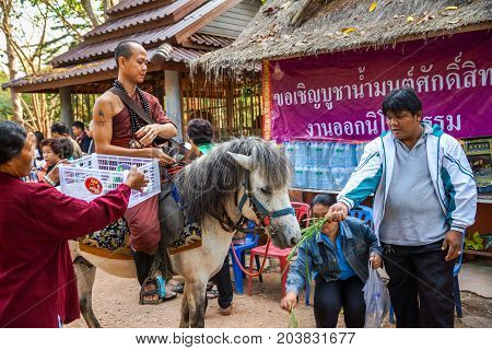 Chiangrai Thailand - February 24 2013: Buddhist monk from Buddhist temple in forest riding on horse to seek alms in rural village of Chiangrai Thailand