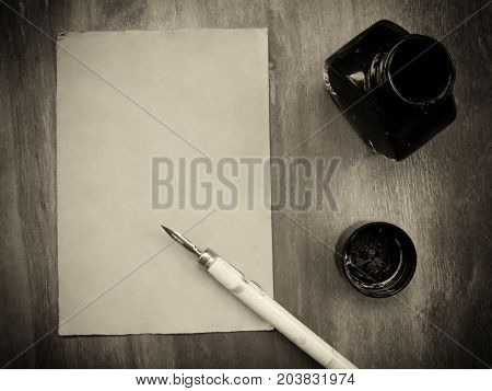 Blank old sheet of paper with a dip pen and an inkwell on a worn wooden background (view from the top or flat lay) retro style in sepia