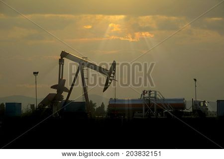 Sunset at oil industry in the field