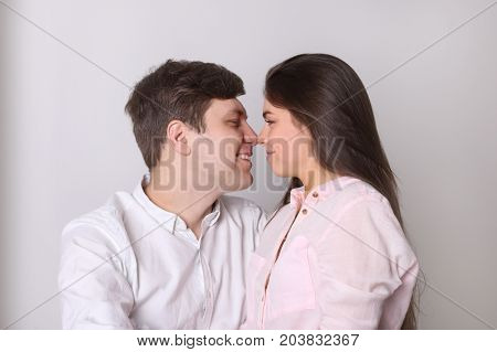 Happy young man and pretty woman in shirts rub their noses in room