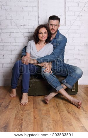 Barefoot man in glasses hugs woman on wooden box in white room