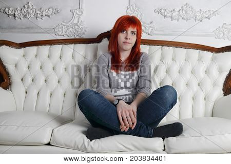 Pretty girl with red hair squats crosslegged on white sofa in white room
