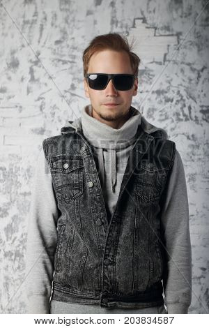 Fashionable young man in sunglasses and denim vest near white wall in studio