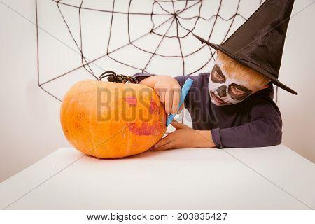 little boy prepare for Halloween party drawing pumpkin, Halloween celebration