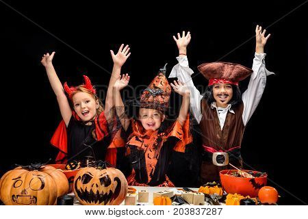 kids in halloween costumes of devil witch and pirate with jack o lanterns and sweets isolated on black
