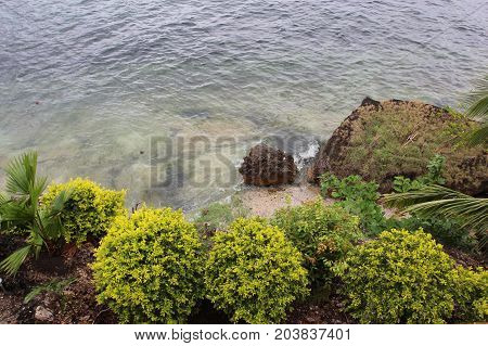 Coast Of The Ocean With Trees, Stones, Buildings In The Foreground. Philippines.
