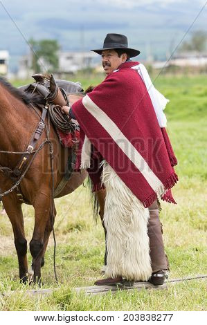 June 3 2017 Machachi Ecuador: cowboy from the andes called 'chagra' arranging horse saddle before a rural rodeo