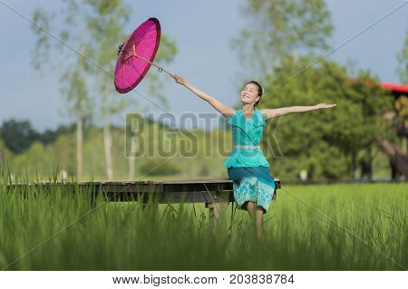 Lao beautiful young woman wearing tradition dress and holding red umbrella sitting on wooden bridge in green rice field happily.