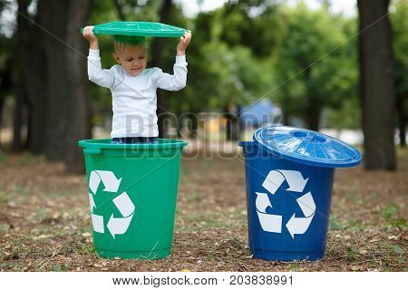 Blue and green bins. Cute preschooler boy, looking inside the trash bin in the street, summer outdoor, save the planet, save the Earth concept. Day in park. Funny babies.