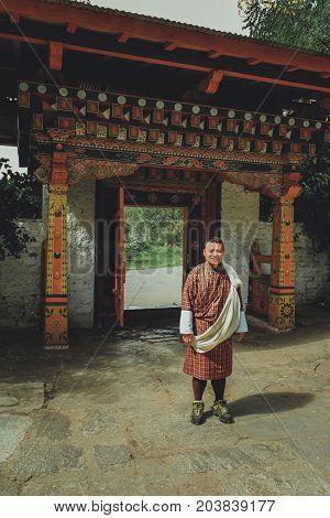 Paro, Bhutan - September 10, 2016: Local Bhutanese Tourist Guide Wearing Traditional Clothing Standi