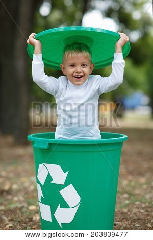 Cute preschooler, standing boy playing with the trash bin lid, in the street, summer outdoor, save the planet, save the Earth concept. Day in park. Funny babies.